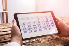 De Digitale Tablet van Businesspersonusing calendar on royalty-vrije stock fotografie