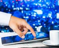 De digitale tablet van de bedrijfsmensenaanraking op bedrijfskrant dichtbij venster stock afbeelding