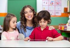 De Digitale Tablet van leraarswith children using bij Bureau Stock Foto's