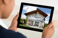 De Digitale Tablet van Person Looking At House On royalty-vrije stock fotografie