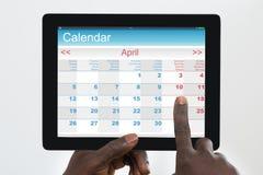 De Digitale Tablet van Person Using Calendar Application On Royalty-vrije Stock Afbeeldingen