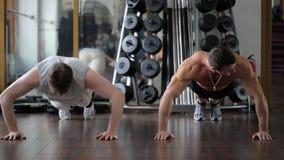 De dikbuikige kerel bekijkt de trainer, die opdrukoefeningen, maar dalingen worstelen te doen toe te schrijven aan uitputting stock videobeelden