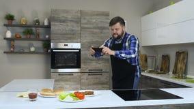 De dikke gebaarde kerel neemt beelden van Ingrediënten voor eigengemaakte hamburger gebruikend een telefoon in een keuken, alvore stock videobeelden