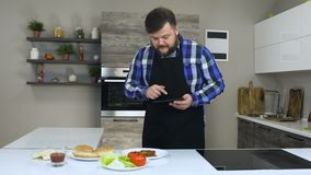 De dikke gebaarde mens controleert of verifieert de ingrediënten voor een hamburger in een keuken stock footage