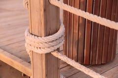 De dikke kabel bond houten steunen op de brug stock afbeelding
