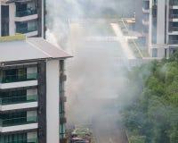 De dikke rook komt uit vensters van de woonhigh-rise bouw stock afbeelding