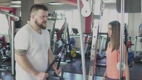 De dikke zwaarlijvige kerel met individuele bus doet fysieke schokken in gymnastiek Te zware mens en de vrouwelijke calorieën van stock video