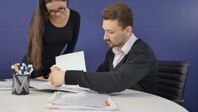 De directeur bespreekt driemaandelijkse financiële verslagen van de firma met secretaresse stock videobeelden