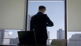De directeur in Bureau op het Werk die zich bij Venster bevinden en bekijkt Zijn Horloge stock footage