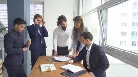 De directeur van het bedrijf houdt een vergadering met zijn ondergeschikten De managers bekijken de documenten in het bureau Coll stock footage