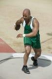 De Discus van atletenpreparing to throw Stock Foto's