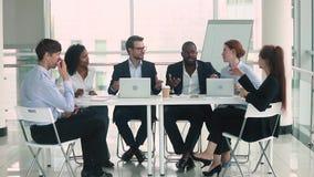 De diverse uitwisseling van ideeën van de bedrijfsmensengroep in groepswerk bij conferentielijst stock videobeelden