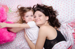 De dochter bereikt voor een zacht stuk speelgoed liggend met haar moeder Stock Foto