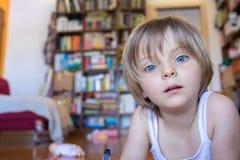 De dochter die van het blondemeisje met blauwe ogen camera in woonkamer bekijken Gelukkig ontspannen gezinsleven met kinderen thu Stock Fotografie