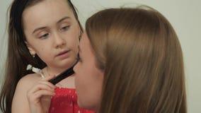 De dochter doet make-up aan mamma stock videobeelden