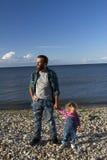 De dochter en de papa ontspannen op het strand Royalty-vrije Stock Foto's