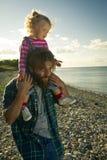 De dochter en de papa ontspannen op het strand Stock Afbeelding