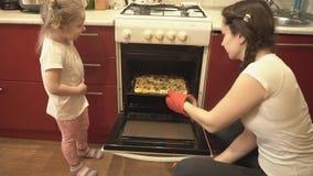 De dochter en haar moeder krijgen uit de ovenpizza stock videobeelden