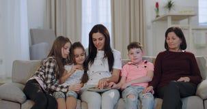De dochter en de kleinkinderen die van de drie generatiesoma op TV letten terwijl het eten van koekjes voor de camerazitting stock video