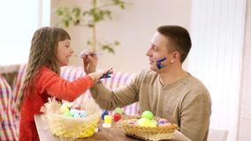 De dochter en de papa bevlekken elkaar met verf, tijdens voorbereiding voor Pasen op de lijst is een mand van eieren en verf stock footage