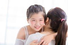 De dochter geeft mamma een omhelzing en een glimlach stock foto's