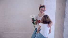 De dochter geeft mamma het boeket van bloemen stock video