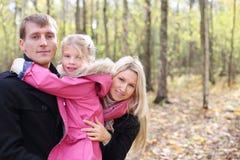 De dochter koestert vader, en de moeder gluurt uit van achter hen stock afbeelding