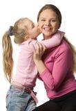 De dochter kust een moeder stock afbeelding