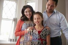 De dochter lichte kaarsen van het oudershorloge op menorah voor Shabbat stock fotografie