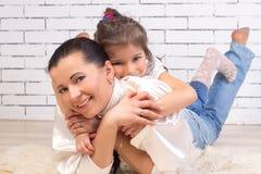 De dochter is op de rug van een moeder stock foto
