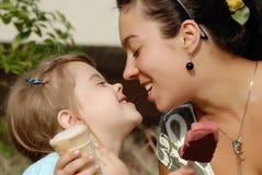 De dochter van het moedervoer met holte een stuk van chocoladeroomijs, familie royalty-vrije stock afbeelding