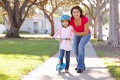 De Dochter van het Onderwijs van de moeder om Autoped te berijden stock afbeelding