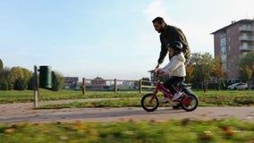 De dochter van het vaderonderwijs om fiets bij stedelijk park te berijden Kindmeisje het leren het biking met de papa` s hulp Fam stock footage