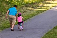 De dochter van het vaderonderwijs om haar fiets te berijden Royalty-vrije Stock Foto