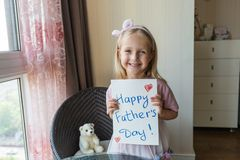 De dochter wenst papa geluk en geeft hem gift en prentbriefkaar Het gelukkige concept van de vaderdag stock foto