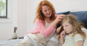 De Dochters van moederpetting leiden terwijl het Meisje dat Laptop Computer, Familiezitting op Bed in Slaapkamer met behulp van T stock footage