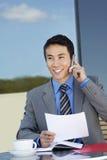 De Documenten van zakenmanon call with bij Openluchtkoffie Stock Afbeelding