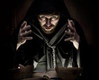 De dodenbezweerder giet werktijden van dik oud boek door kaarslicht op een donkere achtergrond Royalty-vrije Stock Afbeeldingen