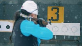 De doelstellingen op een paneel sluiten na dame biathlete schietend hen stock footage