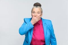 De doen schrikken oude vrouw gesloten mond en heeft grote ogen stock foto