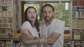 De doen schrikken reactie die van jong paar elkaar omhelzen die vreest en schok ziend iets verschrikking uitdrukken - stock video