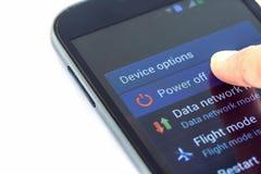 De doigt de presse de mise hors tension bouton sur le smartphone photographie stock libre de droits