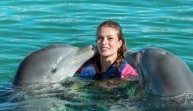 De dolfijnen kussen jonge vrouw in blauw water Glimlachende vrouw die met dolfijn zwemmen De blauwe Abstracte Achtergrond van het stock foto's