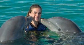 De dolfijnen kussen jonge vrouw in blauw water Glimlachende vrouw die met dolfijn zwemmen De blauwe Abstracte Achtergrond van het stock foto
