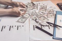 De Dollars die van de bankverenigde staten van het handvatgeld achter grafiek werken toont plannenprobleem van corruptie stock afbeeldingen