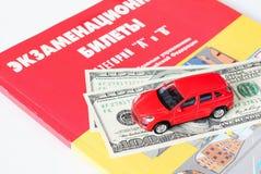 De dollars en de auto zijn aan examenkaartjes stock fotografie