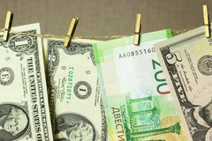 De dollars hangen op de drooglijnwasknijpers in bijlage op een gouden achtergrond Royalty-vrije Stock Afbeelding
