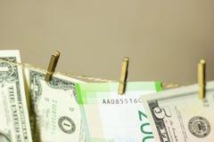 De dollars hangen op de drooglijnwasknijpers in bijlage op een gouden achtergrond Stock Foto's