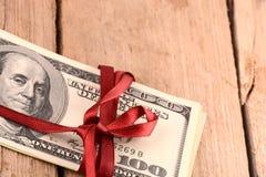 De dollars wraped omhoog met een rood lint Royalty-vrije Stock Foto's