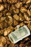 De dollarsbankbiljetten op gouden goudklompjes sluiten omhoog Stock Foto's